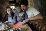 Maggie and Steven Engelsma (cq) and Maggie's son Bryan Espinoza (cq), 8, gather around their...
