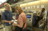(LT. TO RT.)  United Airlines customers Drew Estolar (CQ), of Washington, and Laura Roen (CQ), of...