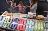 Aliana Martinez-Markey (cq), 2,middle, begs for candy in the check out line while shopping with...