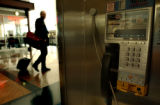 "Travelers walk past ""out of service"" pay phones at Denver International Airport..."