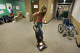 Volunteer Rachel Nance, Governor Bill Owen's Legislative Liason, vacuums the front hallway of one...