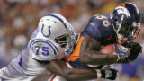 Denver Broncos runningback Mike Anderson, #38, drags Indianapolis Colts defensive tackle Larry...