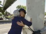 Thelma Gash (cq), left (back to camera), and Ruth Flournoy (cq)  embrace beneath the overpass...
