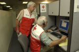 John Roeger, cq, standing, works with Steve Jennison, cq, seated, together on a call to the...