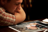 Sean McDonald, cq, Catherine Cathey's brother, looks at photos of his brother-in-law, Second Lt....