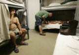 James Main,(cq), 45, of Vernal Utah, left, wakes up in his bunk at a man camp after as he prepares...
