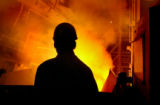(Pueblo, Colo., April 21, 2004)  Gary Bidwell, a melting supervisor,  is silouetted by molten...