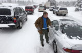 (Monument Hill, Colo.,November 1, 2004) Philip Lincolnhol (cq), of Lakewood, cleans snow off of...