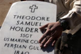 (Denver, Colo., November 19, 2004) Cemetary Caretaker Andrew Alonzo touches the headstone of...