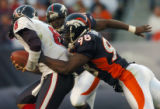 (DENVER., NOVEMBER 7, 2004)  Denver Broncos' #98, Reggie Hayward, right, sacks Houston Texans'...