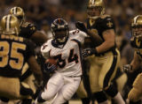 New Orleans Saints defenders watch Denver Broncos runningback Reuben Droughts, #34, cut through...