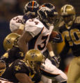 New Orleans Saints linebacker Orlando Ruff, #56, swats at Denver Broncos running back Reuben...