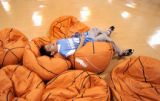 (DENVER, Colo., February 21, 2005) Mike Patterson, 9, of Thornton, rests on a stack of basketball...