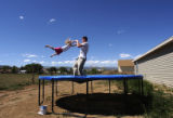 (Vernal, Utah) Jonathan Swain, 21, swings his step daughter Alicia Padigimus, 5, on the trampoline...