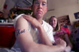 (COLORADO SPRINGS, Colo., February 27, 2005) Justin Lunk (cq), left, 23, shows off a tattoo with...