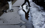 (2/23/05, Aspen, CO) Canadian tourist Mark Elsley hops over a puddle of melted snow while he and...