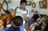 NYT43 - (NYT43) BAGHDAD, Iraq -- March 17, 2005 -- IRAQ-BARBERS-3 -- An Iraqi barber looks out...
