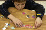 (DENVER, CO., March 24, 2005) Gino Heil (cq according to Tillie Fong) ), 9,  puts a jigsaw puzzle...