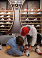 02/19/2005 Denver, Colorado-Anthony Ruiz , 8, Denver, helps his father Rico try on a pair of Air...