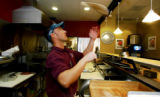 (Ft. Collins, Colo., Mar. 28, 2005) CU Regent Tom Lucero (cq), tosses pizza dough as he prepares...