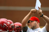 (DENVER, Co., SHOT 9/29/2004) Denver East offensive line coach CJ Remmo (in red ball cap) shows...