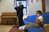 (Denver, Colo., October 31, 2004) Pastor Michael Romero, claps with the music while Manuel...