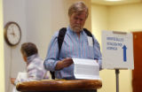 (DENVER, Colo. Oct., 18, 2004) Jay Jone, reads over his ballot before sealing his voted in an...