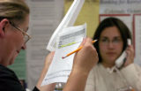 (DENVER, Colo., Oct. 19, 2004) -- Volunteers Emilia Kaplan, left, reads a report while Alexis...