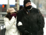 Natasha Johnson and her husband Jason Johnson (cq) try to stay warm as they walk along the 16th...