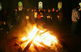 Parishioners and neighbors warm themselves around a bonfire before the Posada, an annual...