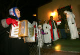 Juanita Malouff-Dominguez (cq), left, of Chama, plays the accordian and leads parishioners in song...