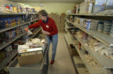 Catherine Busler (cq), a volunteer at Metro CareRing in Denver, fills a cart with food and...