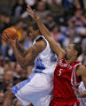 Denver Nuggets center, Marcus Camby, left, grabs down one of his 16 rebounds being defended close...