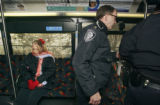 Deborah Davis (cq) sits on an RTD bus after refusing to show her ID to federal police while...