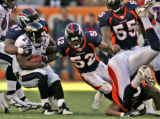 Denver Broncos defensive end Ebenezer Ekuban, right, goes head over heals as teammates (left to...