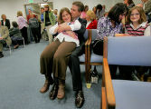 Mike Beasley (cq) the director of the Department of Local Affairs, middle, holds his daughter...