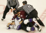 Referees pull Avalanche's Brad May off of Los Angeles' George Parros during a scuffle in the...