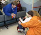 Boise State coach Dan Hawkins talks to Austin Mooneyhan, 5, and his mother, Sherry Mooneyhan,...