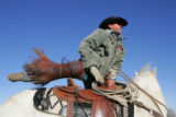 JD Feller, cq, Granbury, Texas, mounts his steed while rounding up horses and cattle on Wednesday,...