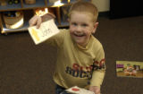 Jared Hebdon,4, (cq), shows how he acts as the teacher picking out fellow classmate names from the...