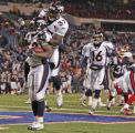 Denver Broncos running back Cecil Sapp, middle, leaps on the back of running back Mike Anderson,...