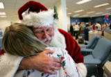 Santa Claus, who also goes by the name Ed Myers of Lakewood, hugs Bonfils apheresis technician...