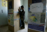 (NYT1) BAGHDAD, Iraq -- Dec. 15, 2005 -- IRAQ-1 -- A child looks on as his mother marks her ballot...