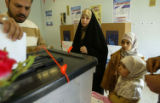 (NYT5) BAGHDAD, Iraq -- Dec. 15, 2005 -- IRAQ-5 -- A man drops his ballot as his family looks on...