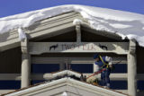 A roofer works on clearing some snow from the roof on the newest addition to the Two Elk Lodge in...