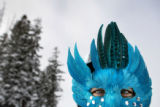 Copper Mountain Ambassador Cindy Muesing, cq, Highlands Ranch, dons a feathered mask while working...