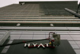 Workers install a Hyatt sign outside the 1,100-room hotel next to the Colorado Convention Center...