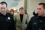 Flanked by police officers, Dan Hawkins, cq, with his wife Misti, cq, arrive at the Byron R. White...