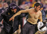 A Buffalo police officer tries to apprehend a unruly fan Bills who ran out onto the field in the...