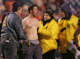 A Buffalo police officers and stadium officals apprehend a unruly fan Bills who ran out onto the...